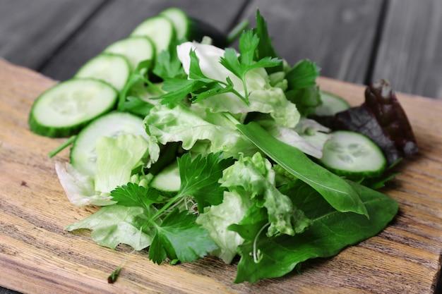 Plasterki ogórka i zieleni na desce do krojenia i powierzchni desek