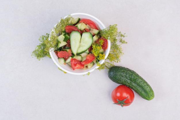 Plasterki ogórków i pomidorów w białej misce z zieleniną.
