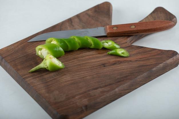 Plasterki ostrej papryczki chili na drewnianej desce do krojenia.