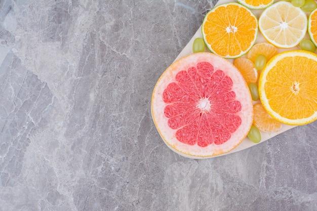 Plasterki owoców cytrusowych i winogron na desce.
