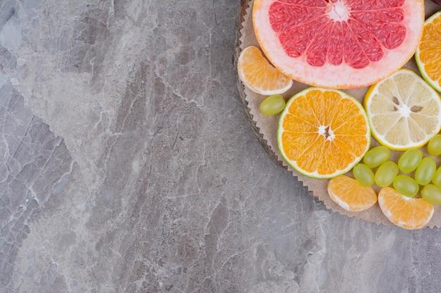 Plasterki owoców cytrusowych i winogron na kawałku drewna.