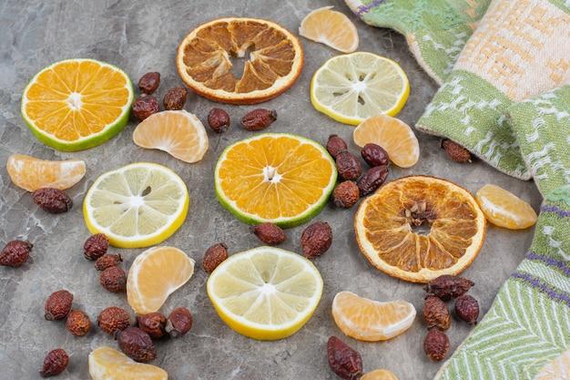 Plasterki owoców cytrusowych z owocami dzikiej róży na powierzchni kamienia.