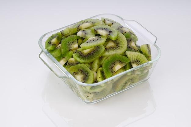 Plasterki owoców kiwi lub pokrojone kawałki ułożone w szklanym kwadratowym pojemniku z białym tłem.