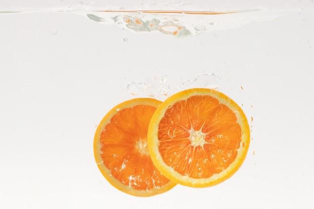 Plasterki owoców pomarańczy wpadające do wody