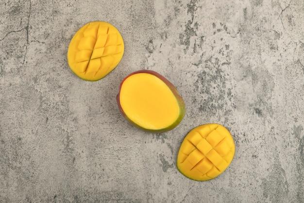 Plasterki owoców tropikalnych mango z kostkami na marmurowej powierzchni.
