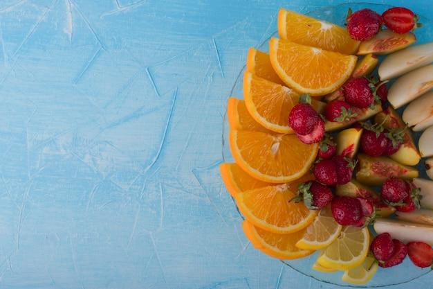 Plasterki owoców ustawić w szklanym talerzu na białym tle na niebieskiej przestrzeni