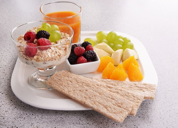 Plasterki owoców z jagodami i musli na stole z bliska