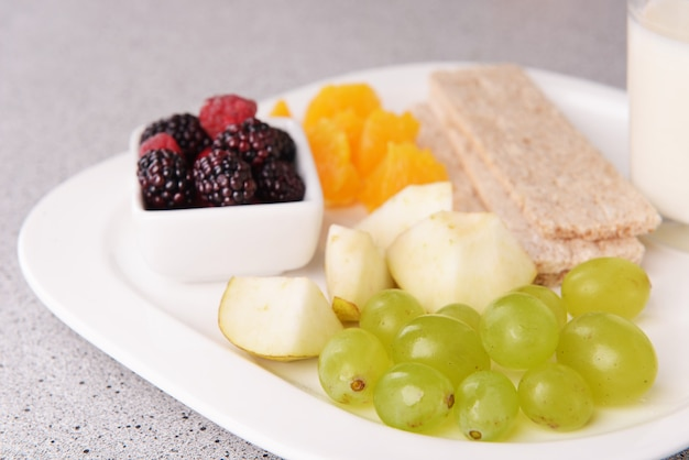 Plasterki owoców z pieczywem chrupkim i szklanką mleka na talerzu na stole z bliska
