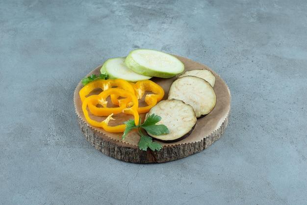 Plasterki papryki, bakłażana i cukinii na drewnianym kawałku.