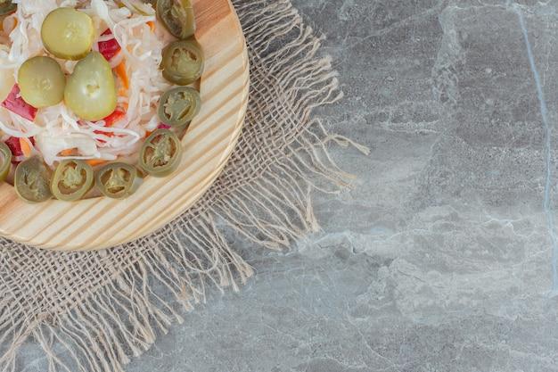 Plasterki papryki i kapusty kiszonej na drewnianym talerzu.