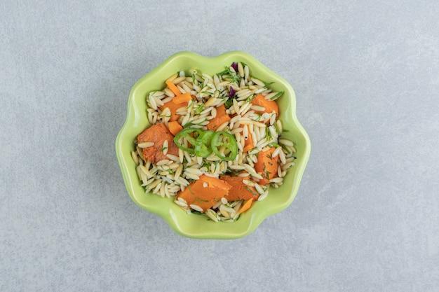 Plasterki papryki, marchewki z ryżem w misce, na marmurze.