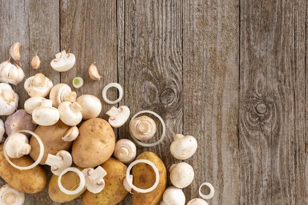 Plasterki pieczarek i ziemniaków na drewnianym stole.