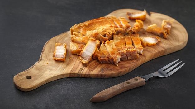 Plasterki pieczonej chrupiącej wieprzowiny na drewnianej desce do krojenia