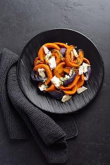Plasterki pieczonej dyni, cebula, czosnek, przyprawy i plasterki sera dorblu na czarnym talerzu ceramicznym i starym czarnym kamieniu