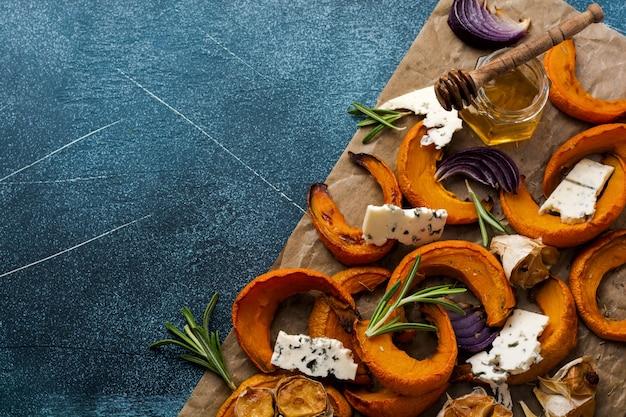 Plasterki pieczonej dyni, cebula, czosnek, przyprawy i plasterki sera dorblu na pergaminie i starym niebieskim kamieniu