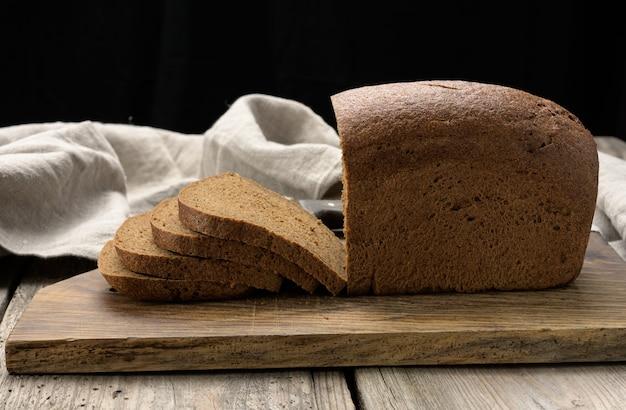 Plasterki pieczony prostokątny chleb z mąki żytniej na brązowej desce, zdrowa żywność