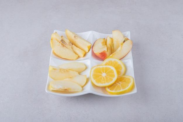 Plasterki pigwy, jabłka, gruszki i cytryny na danie na marmurowym stole.
