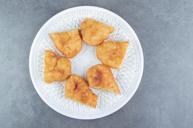 Plasterki piroshki z ziemniakami na białym talerzu.
