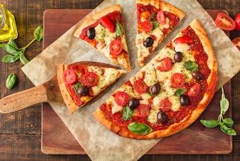 Plasterki pizzy na marmurze nad deską do krojenia