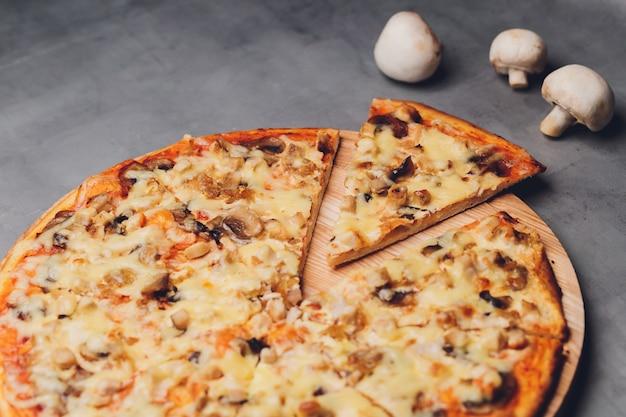 Plasterki pizzy na rustykalnej drewnianej tacy i ciemnym tle.