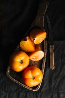 Plasterki pomarańczowi pomidory na tnącej desce i nożu