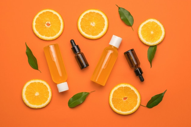Plasterki pomarańczy, butelki medycyny i butelki soku na pomarańczowym tle.