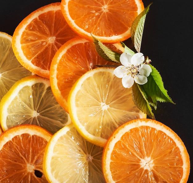 Plasterki pomarańczy i cytryny, odizolowane na czarno.