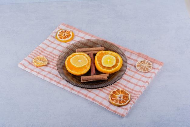 Plasterki pomarańczy i cytryny w szklanej misce z laskami cynamonu.