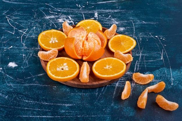 Plasterki pomarańczy i mandarynek na białym tle na drewnianym talerzu na niebieskim tle. wysokiej jakości zdjęcie