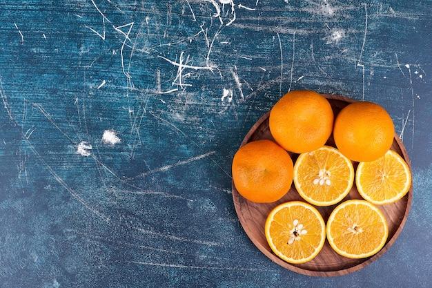 Plasterki pomarańczy i mandarynek na drewnianym talerzu na niebieskim tle. wysokiej jakości zdjęcie
