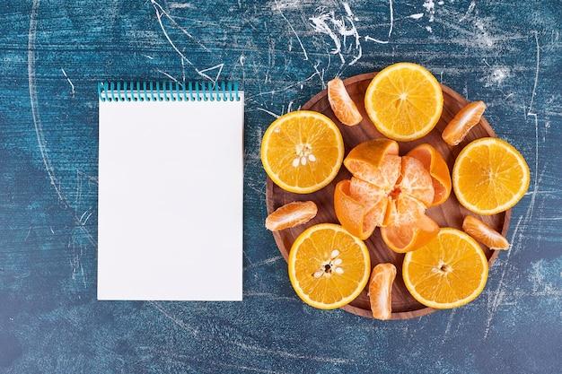 Plasterki pomarańczy i mandarynek na drewnianym talerzu z notatnikiem na boku. wysokiej jakości zdjęcie