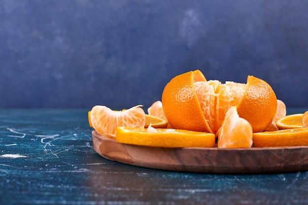 Plasterki pomarańczy i mandarynek na drewnianym talerzu