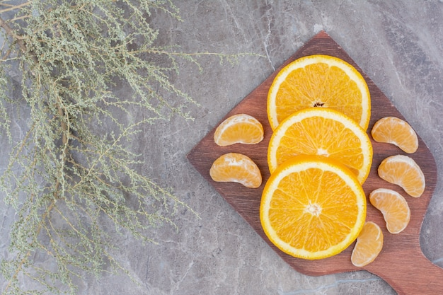 Plasterki pomarańczy i mandarynki na desce.