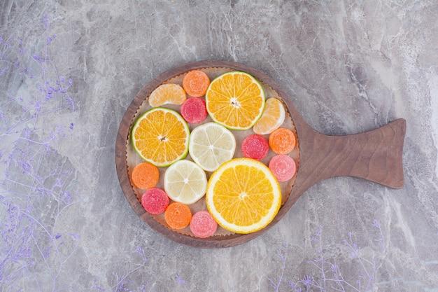 Plasterki pomarańczy, mandarynki i cukierki na desce do krojenia.