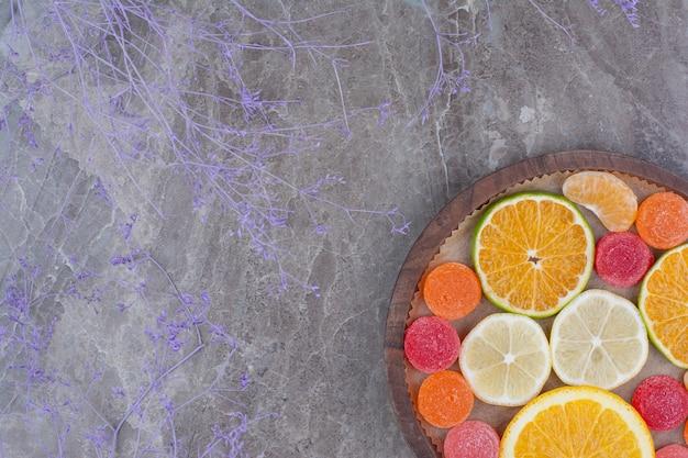 Plasterki pomarańczy, mandarynki i cukierki na drewnianym talerzu.