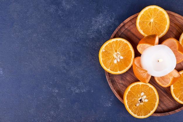 Plasterki pomarańczy na białym tle na drewnianym talerzu. wysokiej jakości zdjęcie