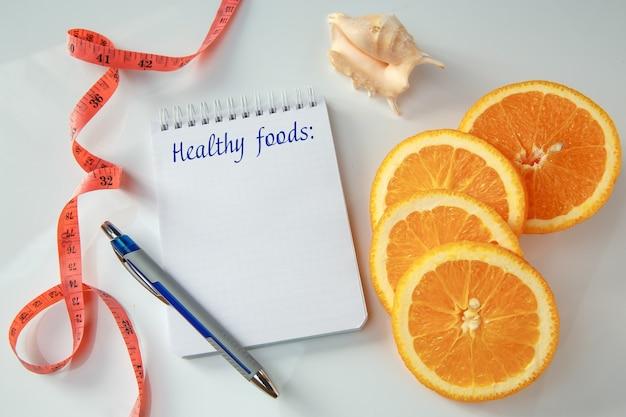 Plasterki pomarańczy, pusta notatka z długopisem i miarką. pojęcie diety