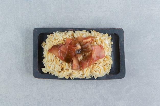 Plasterki pomidorów na ryżowym drewnianym talerzu, na marmurowym tle.