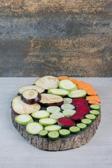Plasterki różnych warzyw na drewnianym kawałku. wysokiej jakości zdjęcie