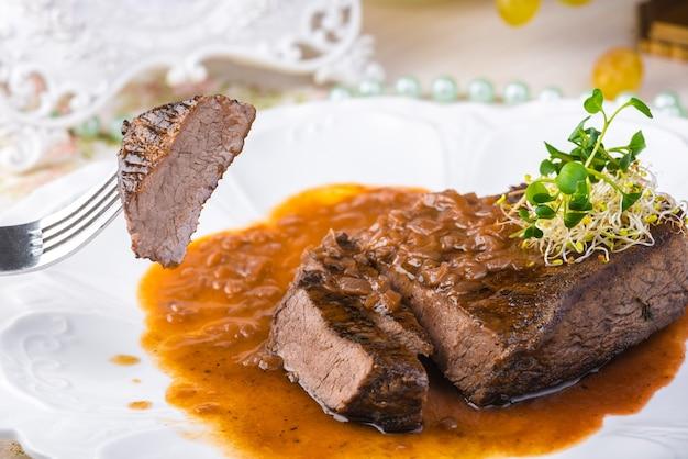 Plasterki rzadkiego grillowanego steku wołowego ribeye z sosem na białym talerzu. selektywna ostrość.