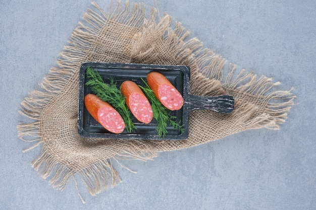 Plasterki salami na czarnej desce do krojenia.
