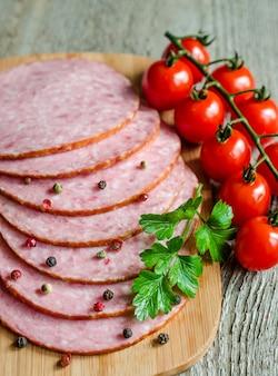 Plasterki salami na desce do krojenia z pomidorami