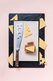 Plasterki sera i świeżego chleba na kamiennej desce do krojenia z nożem do sera.