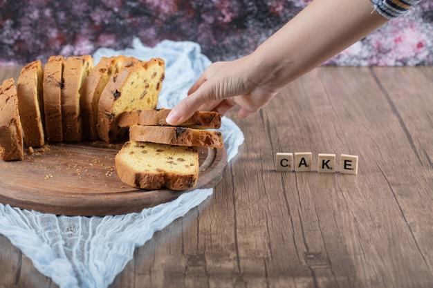 Plasterki słodkie ciasto na białym tle na drewnianej desce.