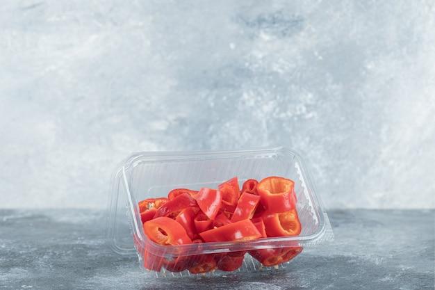 Plasterki słodkiej czerwonej papryki na plastikowym talerzu.
