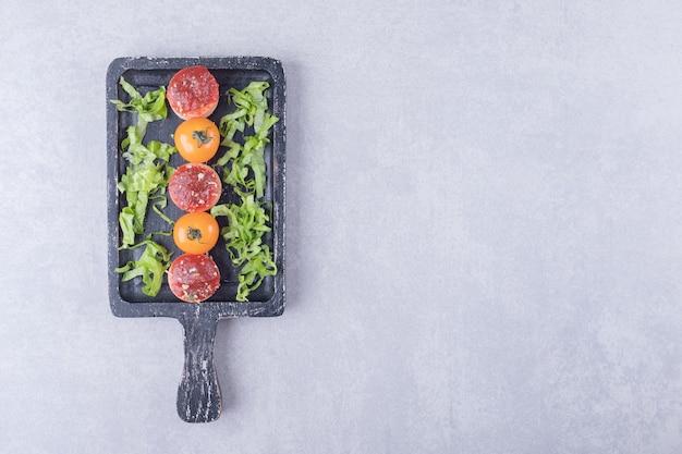 Plasterki smaczne kiełbaski z keczupem i pomidorami na czarnej tablicy.