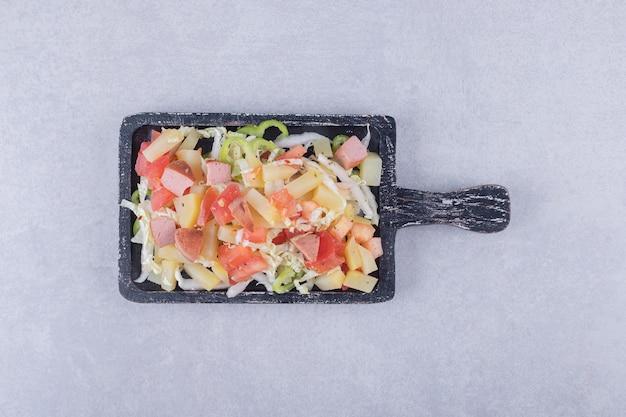 Plasterki smaczne kiełbaski ze świeżą sałatą na czarnej tablicy.