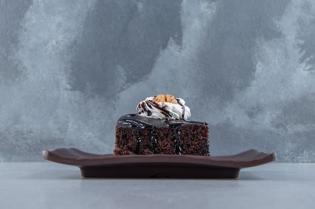 Plasterki smacznego czekoladowego brownie z kremem na ciemnym talerzu