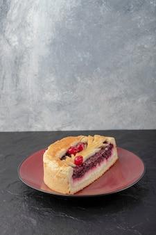 Plasterki smaczny sernik z jagodami umieszczony na czerwonym talerzu.