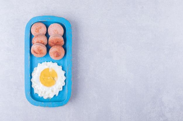 Plasterki smażone kiełbaski i jajko na niebieskim talerzu.